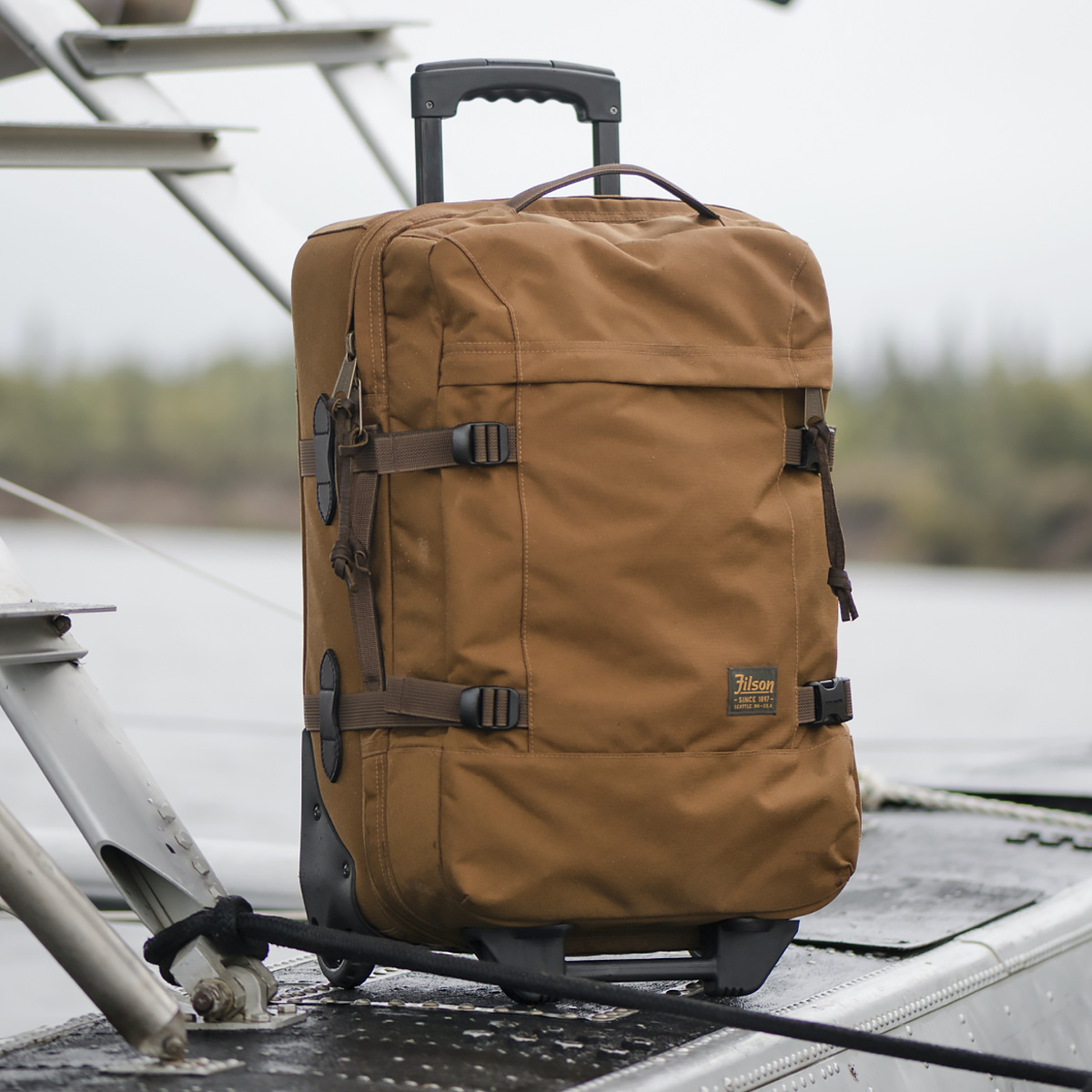 Filson Dryden Dryden 2-Wheel Rolling Carry-On Bag 20047728-Whiskey, built with abrasion-resistant ballistic nylon for years of reliable travel