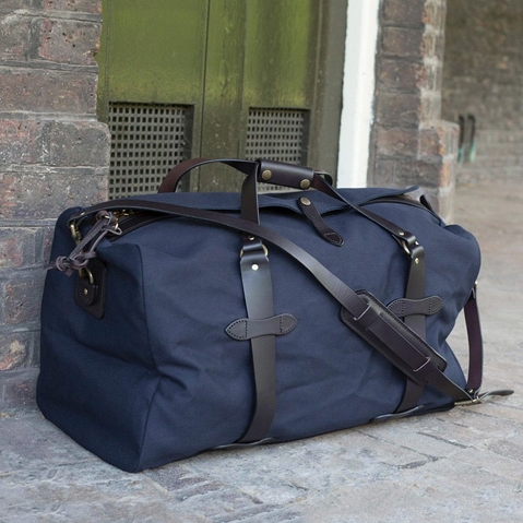 Filson Duffle Small Navy 11070220, a water-resistant, heavy-duty duffle with leather accents that meets airline carry-on size restrictions