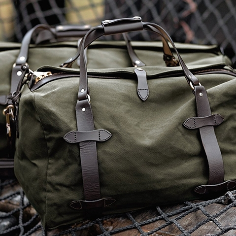 Filson Duffle Small Otter Green 11070220, a water-resistant, heavy-duty duffle with leather accents that meets airline carry-on size restrictions