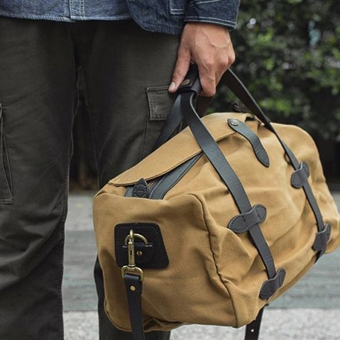 Filson Duffle Small Tan 11070220, a water-resistant, heavy-duty duffle with leather accents that meets airline carry-on size restrictions
